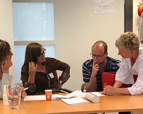 4 mensen aan een vergadertafel